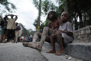 Injured people sit along a road the day after the earthquake struck Port-au-Prince, Haiti, (AP Photo/Jorge Cruz)